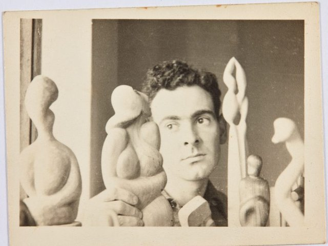 An image of Robert Klippel with a group of his early carvings