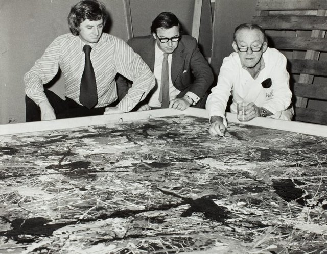 An image of James Mollison and Peter Laverty watching conservator William Boustead examining 'Blue Poles' 1952 by Jackson Pollock