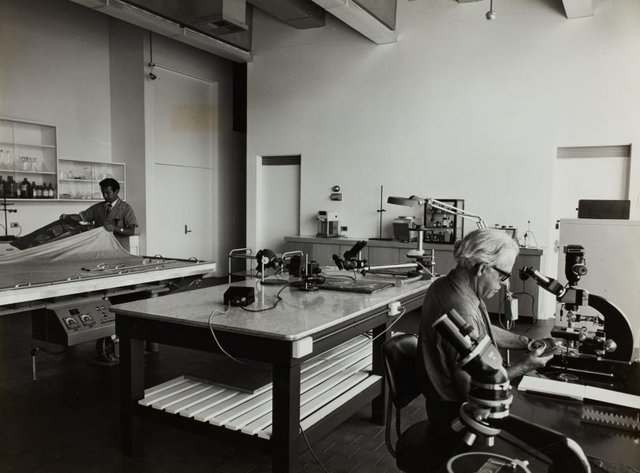 An image of Historical interior view of the conservation laboratory of the Art Gallery of New South Wales, showing micro-photography equipment on the right and the vacuum hot-press table on the left