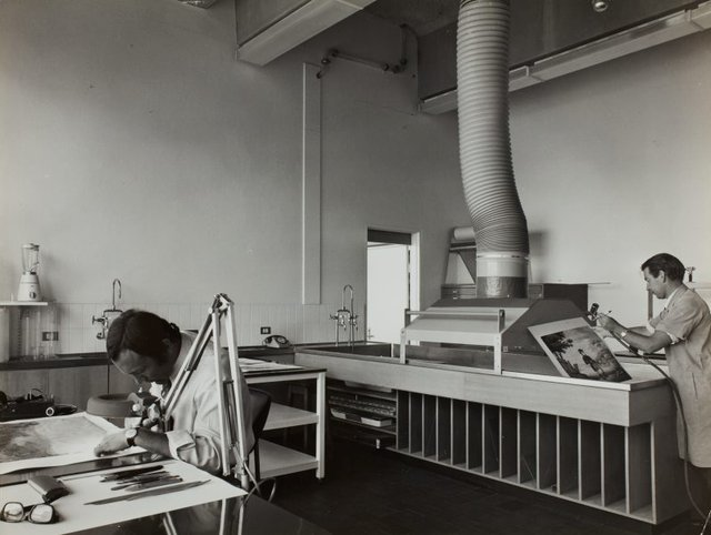 An image of Historical interior view of the paper conservation section of the Art Gallery of New South Wales, showing retouching work proceeding on the left and spray-bleaching on the right