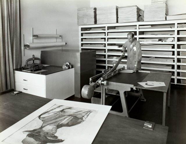 An image of Historical interior view of the mount cutting room of the Art Gallery of New South Wales with mount cutter Bill Lamont at work