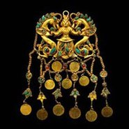 Image: One of a pair of pendants showing the 'Dragon Master'; gold, turquoise, garnet, lapis lazuli, carnelian, pearls; 12.5 × 6.5 cm. Tillya Tepe, 1st century AD, National Museum of Afghanistan. Credit: Thierry Ollivier