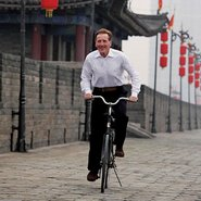 Image: Edmund Capon rides a bicycle on the wall of the ancient city of Xi'an on 23 October 2010. Photo by Kevin Lee/Getty Images for Good Weekend