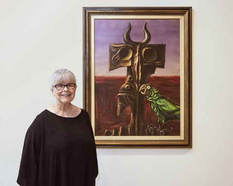 Barbara Jools with the painting she and her late husband Dr Nic Jools have gifted to the Art Gallery of NSW, Albert Tucker's *The Intruder* (1964)