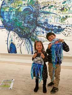 Two kids with art they have made in front of an artwork