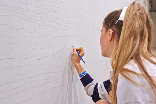 A student carefully draws her line on the wall, making sure not to touch the lines on either side. She is also trying to apply a consistent pressure and often rotates the pencil to keep the line a consistent thickness and hue.