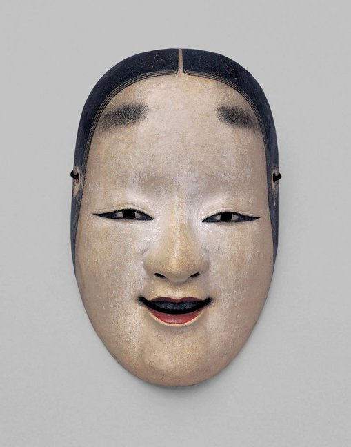 Nō mask Ko-omote, Edo period, 17th centuryNational Noh Theatre  	This mask portrays the features of a sweet young woman. One trait of the ko-omote mask is the three strands of hair that fall naturally from the top of the forehead. This is mask is used for various young female roles in different plays depending on the wishes of the actor.